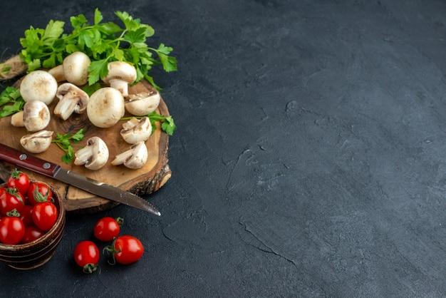 나무 판자 흰 수건에 있는 생 버섯과 채소 칼, 여유 공간이 있는 검정색 배경에 있는 그릇에 신선한 토마토의 전면 보기