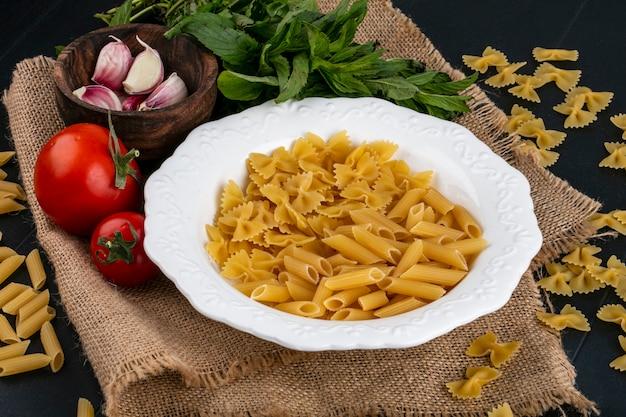 Вид спереди сырых макарон в тарелке с помидорами, чесноком и пучком мяты на бежевой салфетке