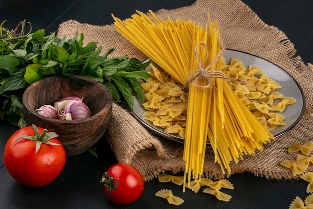Вид спереди сырых макарон с сырыми спагетти на тарелке с помидорами, чесноком и пучком мяты на бежевой салфетке