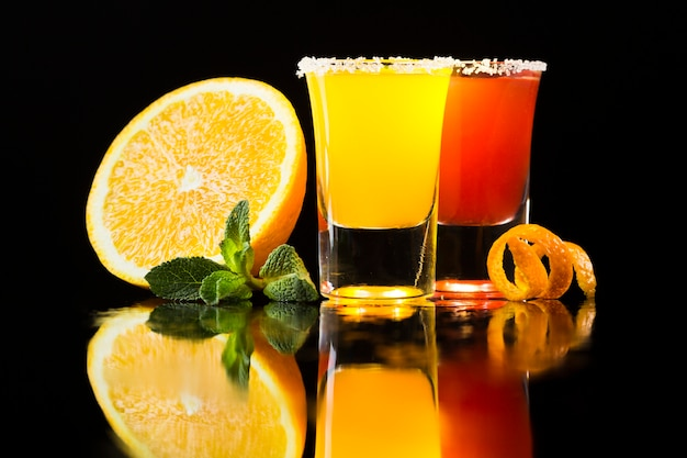 Вид спереди красный и желтый коктейль в рюмки с апельсином