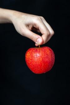 暗い表面で手に赤いリンゴの正面図
