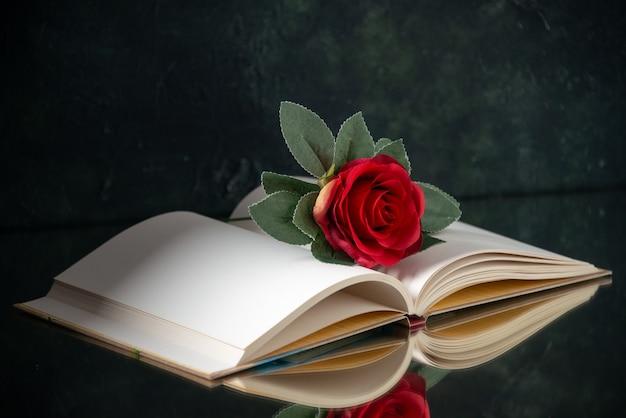 Вид спереди красного цветка с открытой книгой на черном