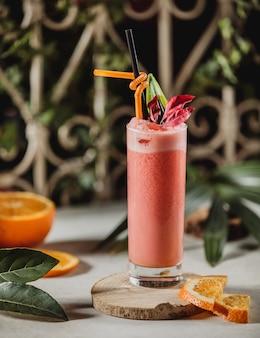 テーブルの上の木製のスタンドにストローとスライスしたオレンジのグラスに赤いグレープフルーツのスムージーの正面図