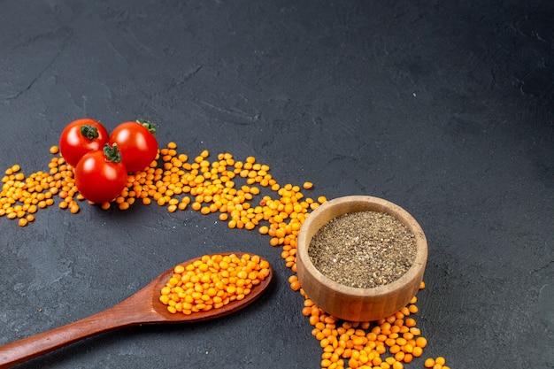 여유 공간이 있는 검은색 배경에 빨간색 렌즈콩과 토마토 후추의 전면 보기