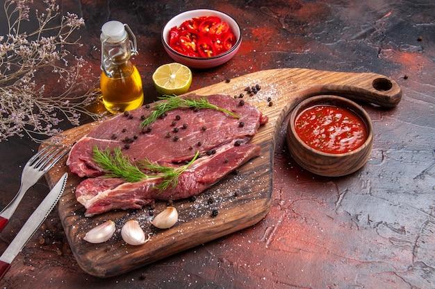 Вид спереди красного мяса на деревянной разделочной доске и чеснока, вилки и ножа с зеленым перцем на темном фоне