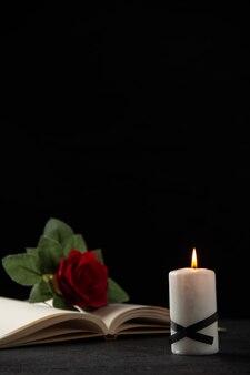 Вид спереди красной розы с книгой и свечой на черном