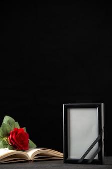 Вид спереди красной розы с книгой и картинной рамкой на черном