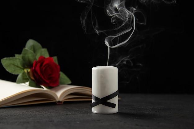 Вид спереди красной розы со свечой и книгой на черном