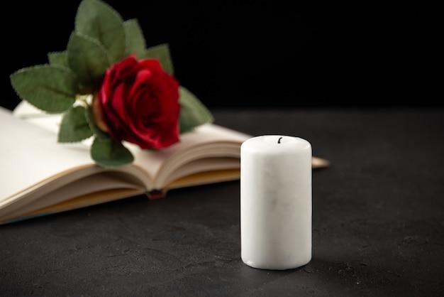 Вид спереди красной розы с открытой книгой и свечой на черном