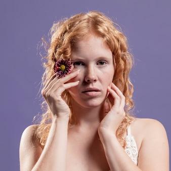 그녀의 손과 꽃과 함께 포즈를 취하는 빨간 머리 여자의 전면보기