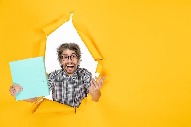 노란색 찢어진 벽에 파일이 있는 일반 남성의 전면 보기