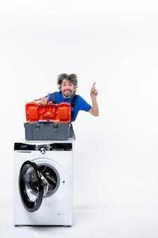 흰 벽에 있는 세탁기 바로 뒤를 가리키는 도구 가방을 여는 기뻐하는 수리공의 전면 모습