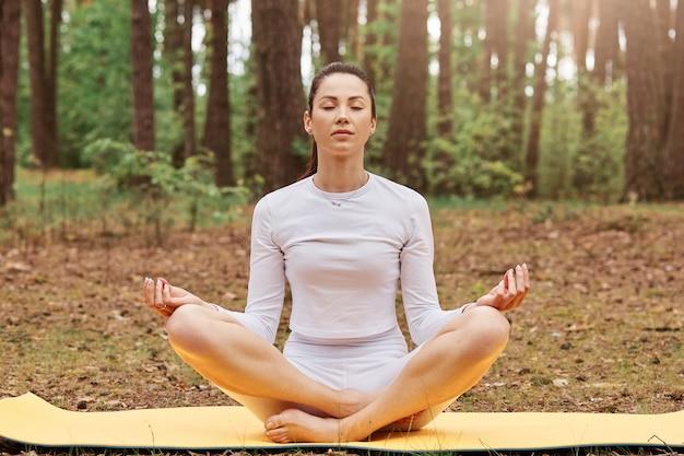 ポニーテールの髪型でマットの上に蓮のポーズで座っているリラックスしたスポーティな女の子の正面図、目を閉じたまま、足を組んで