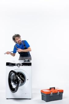흰 벽에 세탁기 뒤에 서 있는 양손으로 청진기를 들고 수리공의 전면 보기