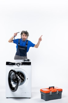 흰 벽에 있는 세탁기 뒤에 서 있는 무언가를 가리키는 청진기가 있는 수리공의 전면 모습