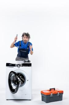 白い壁の洗濯機の後ろに立って聴診器を上げて手を上げている修理工の正面図