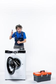 白い壁の洗濯機を指して後ろに立っている聴診器を持つ修理工の正面図