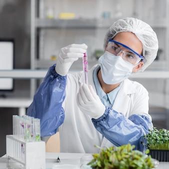 Вид спереди исследователя с пробиркой и растением в лаборатории биотехнологии