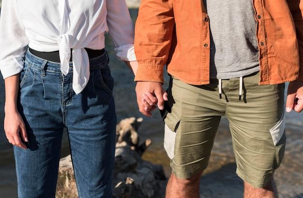 ビーチで手をつないでロマンチックなカップルの正面図