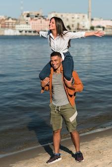 ビーチで時間を過ごすロマンチックなカップルの正面図