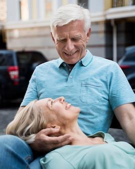 屋外のベンチで自分の時間を楽しんでいるロマンチックな年配のカップルの正面図
