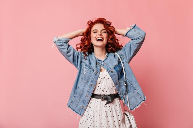 Вид спереди романтичной женщины, смеющейся на розовом фоне. студийный снимок добродушной девушки в повседневной джинсовой куртке.