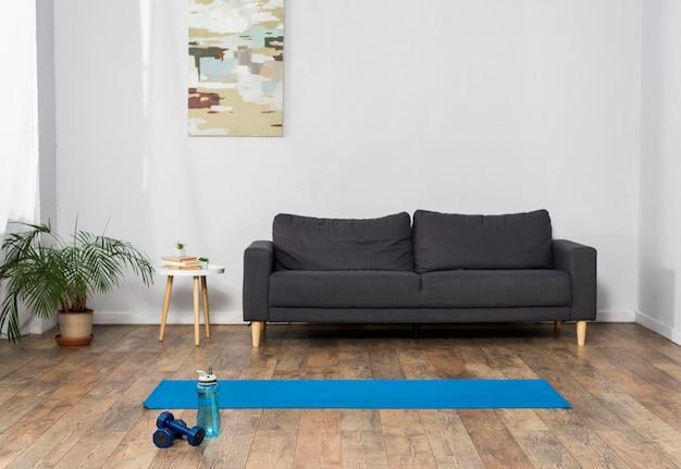 Вид спереди интерьера комнаты с весами и бутылкой с водой