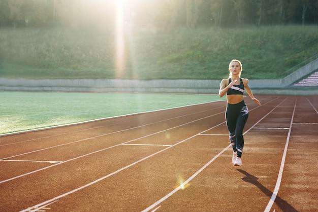 스포츠 트랙에서 유산소 운동을 하는 검은색 운동복을 입은 백인 여성의 전면 모습