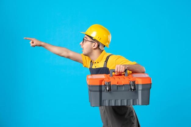 青の彼の手でツールボックスと制服を着て実行中の男性ビルダーの正面図