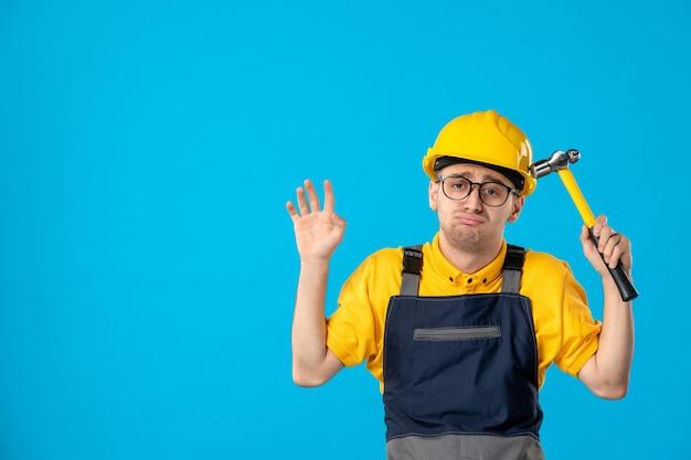 Вид спереди грустного мужчины-строителя в форме с молотком в руках на синем