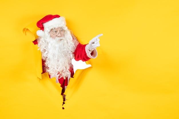 찢어진 된 종이 노란색 벽을 통해 찾고 산타 클로스의 전면보기
