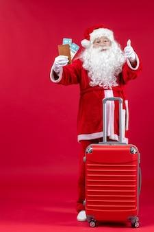 Вид спереди санта-клауса с сумкой, держащей билеты и готовящейся к поездке на красной стене