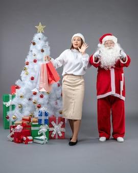 クリスマスツリーの周りの女性と灰色の壁にプレゼントとサンタクロースの正面図