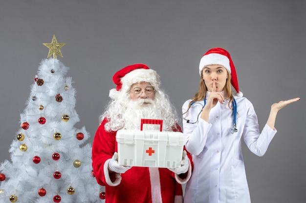 Вид спереди санта-клауса с женщиной-врачом, которая дала ему аптечку на серой стене