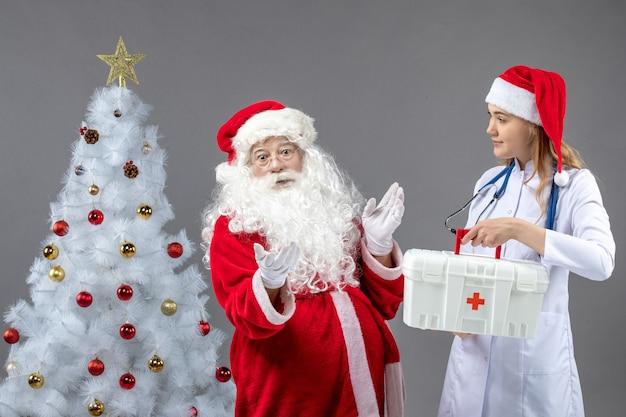 Вид спереди санта-клауса с женщиной-врачом, держащей аптечку на серой стене