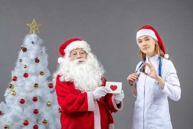 灰色の壁に丸薬と小さなフラスコを保持している女性医師とサンタクロースの正面図