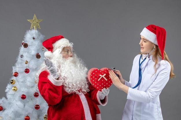 Вид спереди санта-клауса с женщиной-врачом, которая наблюдает за настоящим со стетоскопом на серой стене
