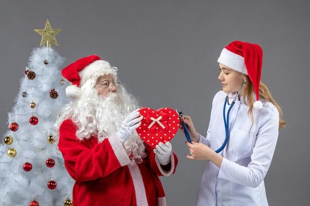 Вид спереди санта-клауса с женщиной-врачом, которая наблюдает со стетоскопом на серой стене