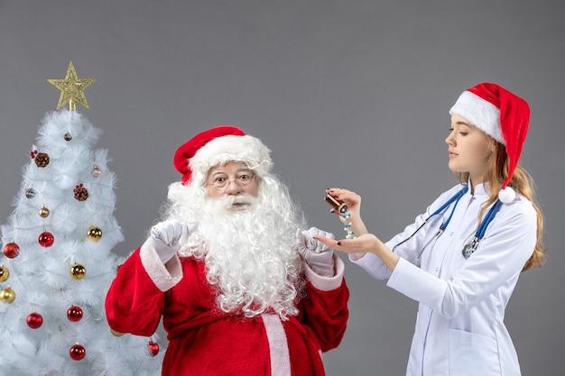회색 벽에 약을 붓는 여성 의사와 산타 클로스의 전면보기