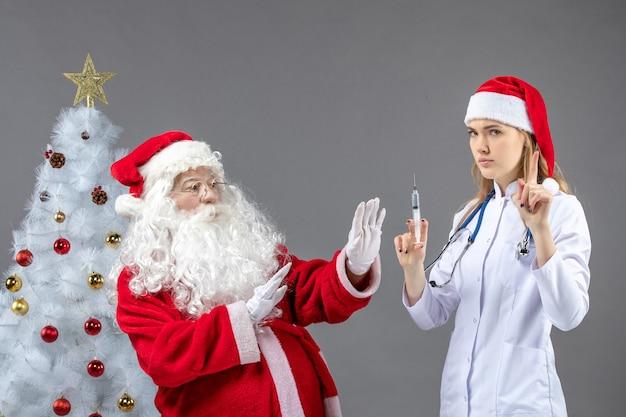 Вид спереди санта-клауса с женщиной-врачом, которая готовит инъекцию на серой стене
