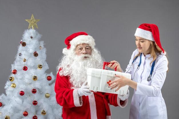 Вид спереди санта-клауса с женщиной-врачом, которая берет от него аптечку на серой стене