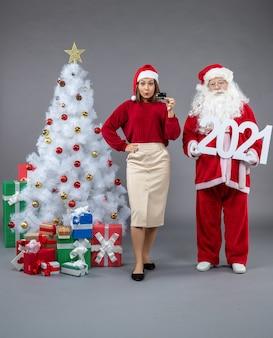 회색 벽에 2021 보드와 은행 카드를 들고 여성과 산타 클로스의 전면보기