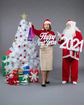 회색 벽에 여성 지주 및 새해 복 많이 받으세요 쇼핑백과 산타 클로스의 전면보기