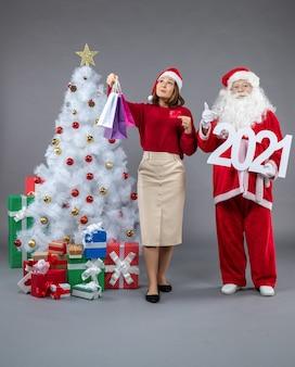 灰色の壁に買い物袋と2021ボードを保持している女性とサンタクロースの正面図