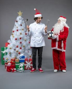 크리스마스 주위 남성 요리사와 산타 클로스의 전면보기 회색 벽에 흥분 선물