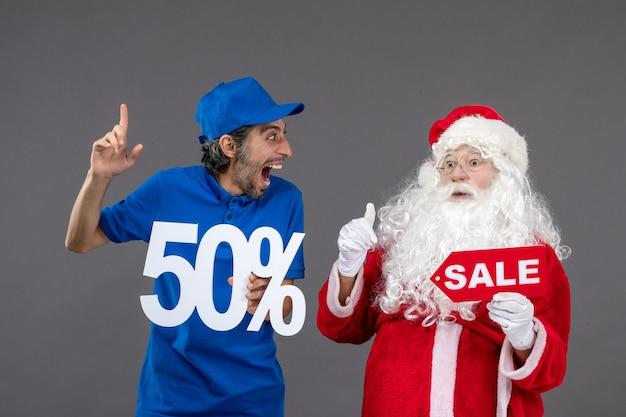 Вид спереди санта-клауса с мужчиной-курьером, держащим 50%, и распродажами на серой стене