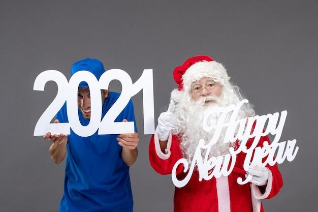 Вид спереди санта-клауса с мужчиной-курьером, держащим доски с новым годом и 2021 годом на серой стене