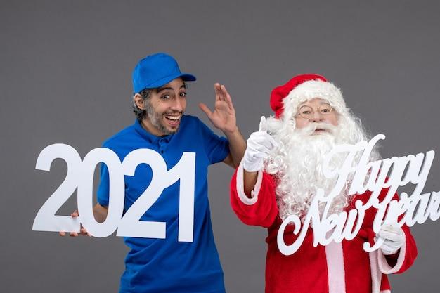 회색 벽에 남성 택배 지주와 새해 복 많이 받으세요 2021 보드와 산타 클로스의 전면보기