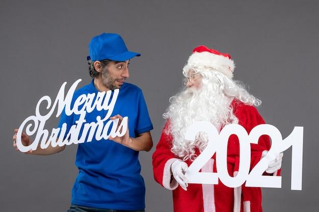 회색 벽에 메리 크리스마스와 2021 배너를 들고 남성 택배와 산타 클로스의 전면보기