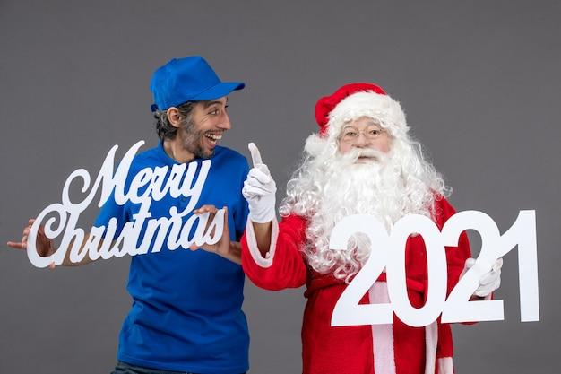 회색 벽에 메리 크리스마스와 2021 보드를 들고 남성 택배와 산타 클로스의 전면보기